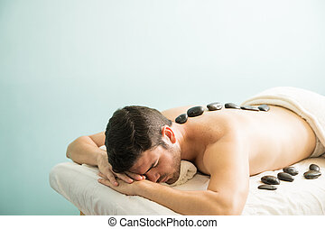 Man with hot stones in a spa