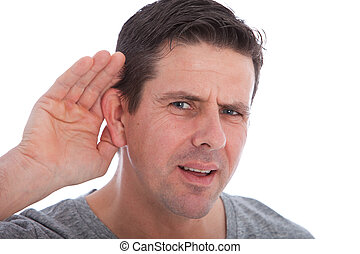 Man with impaired hearing struggling to hear frowning as he ...