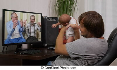 man with infantat home having video chat on PC, interacting together online during social distancing and self isolation in quarantine lockdown