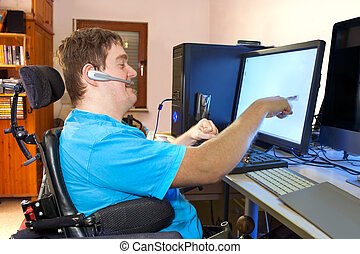 Spastic young man with infantile cerebral palsy caused by a complicated birth sitting in a multifunctional wheelchair using a computer with a wireless headset reaching out to touch the touch screen