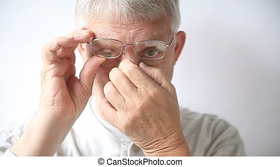 man with irritation from nose pads - an older man rubs the...