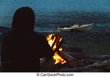 Man with kayak near campfire on the beach in the evening