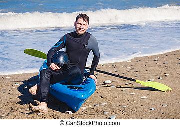 Man with kayak on the beach