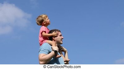 Man with kid on shoulders pointing away