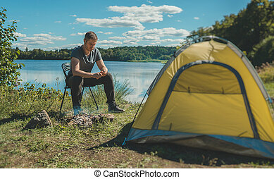 Man with knife cutting wooden stick near camping tent by the lake.
