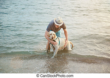 Man with labrador dog in water