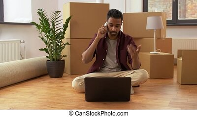 man with laptop and boxes calling on phone at home