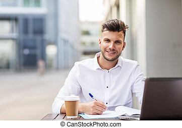 man with laptop and coffee at city cafe - business,...