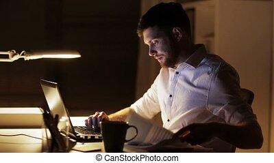 man with laptop and smartphone at night office