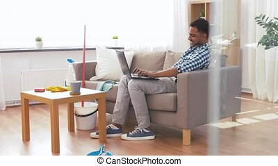 man with laptop computer after home cleaning - household,...