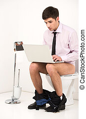 Man with laptop computer sitting on toilet. Businessman typing letter on notebook while sitting on toilet