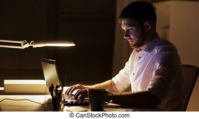 man with laptop finishing work at night office - business,...