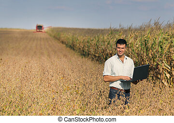 Man with laptop in soybean field - Young landowner with...