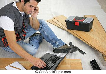 Man with laptop laying laminate flooring