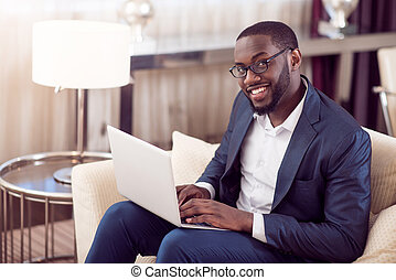 Man with laptop looking at camera