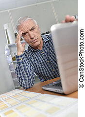 Man with laptop, looking troubled