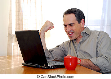 Man with laptop - Man sitting at a desk and looking into his...