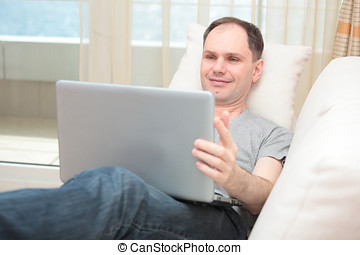 Man with laptop on a sofa