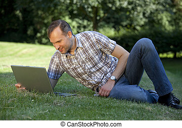man with laptop on the grass