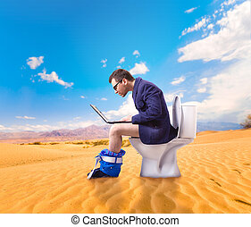 Man with laptop sitting on toilet bowl in desert