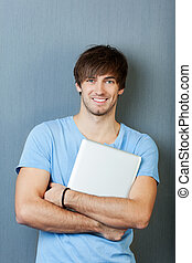 Man With Laptop Standing Against Blue Wall