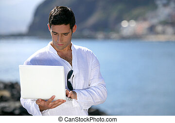 Man with laptop standing outdoors
