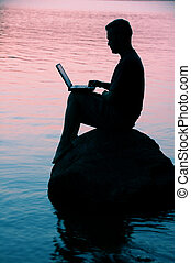 Man with laptop - sitting on a rock on a lake