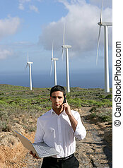 Man with laptop stood by wind farm