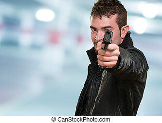 man with leather jacket pointing with gun in a garage