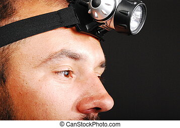 close detail of a man with LED Head Lamp isolated on black background