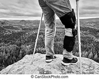 Man with leg in knee cages and crutches for stabilization stay on rock. Hurt tourist walk in mountains