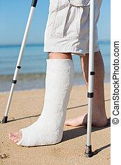 Man with leg plaster at a beach