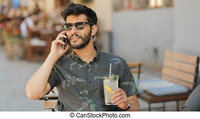 Man with Lemonade Talks on Phone - Attractive asian man...