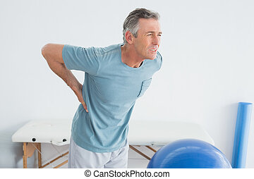 Man with lower back pain at the gym hospital - Mature man...