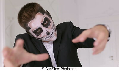 Man with make-up skeleton creepy looking at the camera, and stretches his hands.