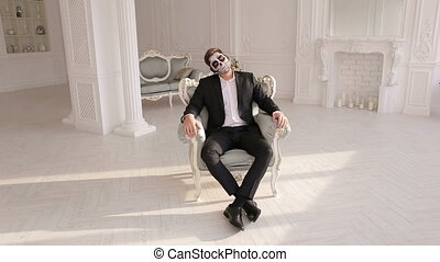 Man with make-up skeleton sitting in the old grey chair in the vintage room.