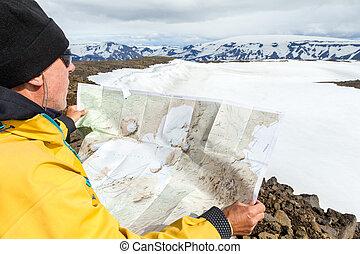 Man with map exploring wilderness on trekking adventure.
