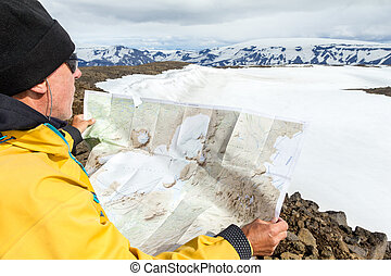 Man with map exploring wilderness on trekking adventure.