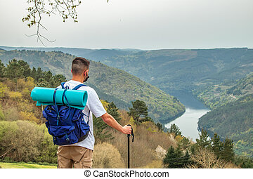 man with mask and backpack hiking in the mountain looking at the landscape