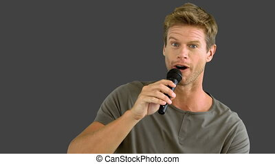Man with microphone singing on grey