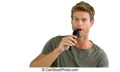 Man with microphone singing on white background in slow...