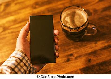 Man with mobile and dark beer mug