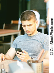 Man with mobile phone in restaurant