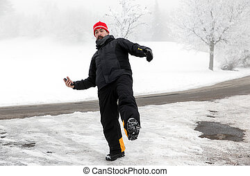 Man with mobile phone is slipping on a freezy street - Man...