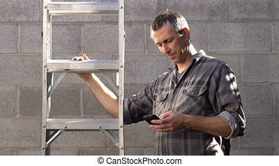 Man With Mobile Phone Puts Down Ladder - Man holding a...