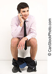 Man with mobile phone sitting on toilet. Businessman talking on phone while sitting on toilet