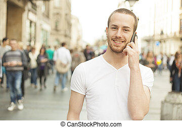 Man with mobile phone walking on street