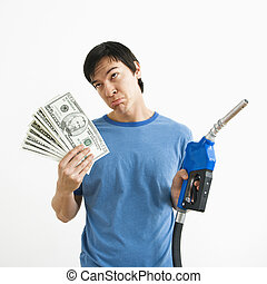 Man with money and gas nozzle. - Asian young man with sad...