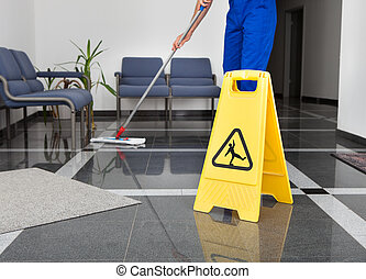 Man With Mop And Wet Floor Sign - Close-up Of Man Cleaning...