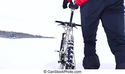 Man with mountain bike on snowy filed. Biker is pushing bike in deep snow. Cloudy winter day with gentle wind and small snow flakes in the air.